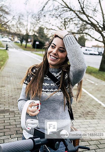 Lächelnde junge Frau mit Kopfhörern und Elektroroller in der Stadt