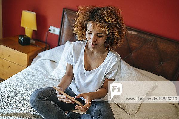 Junge Frau mit lockigem Haar sitzt mit Tablette auf dem Bett