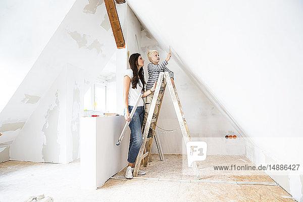 Mutter und Sohn arbeiten am Dachbodenausbau