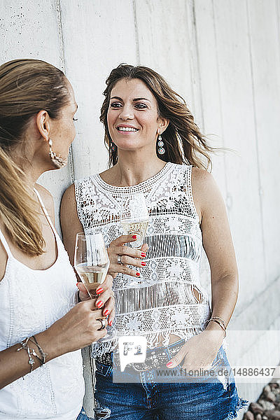 Two best friends drinking champagne outdoors