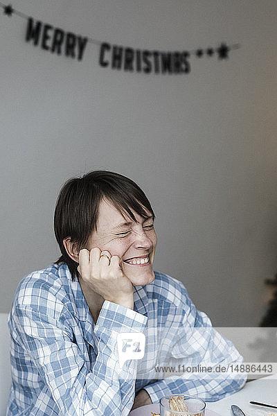 Porträt einer lachenden Frau  die zur Weihnachtszeit am Frühstückstisch sitzt