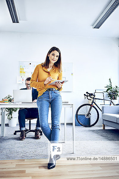 Portrait of businesswoman using tablet in office with colleague in background