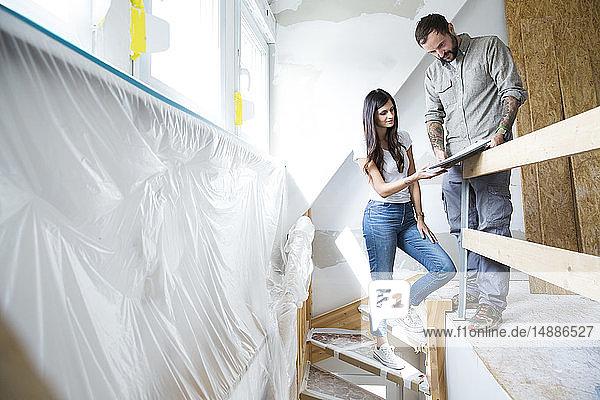 Ehepaar auf dem Dachboden  das renoviert werden soll und in Kataloge schaut
