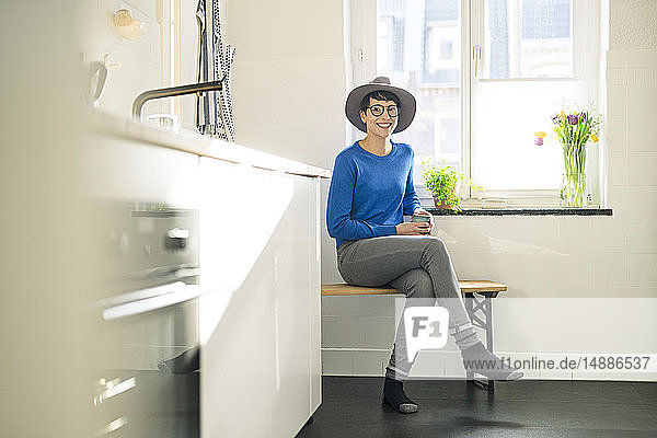 Portrait of smiling sitting on bench in kitchen at the window
