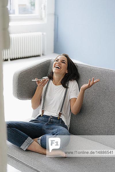Hübsche Frau sitzt auf der Couch  benutzt ein Smartphone und lacht