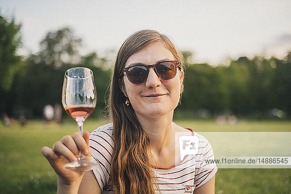 Porträt einer lächelnden Frau mit Sonnenbrille  die im Stadtpark mit einem Glas Wein anstößt