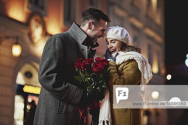 Mann schenkt seiner verblüfften Freundin am Valentinstag einen Strauß roter Rosen