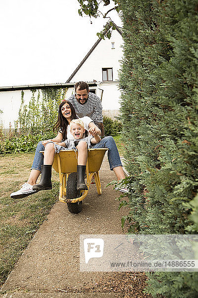 Playful man pushing wife and son sitting in wheelbarrow in garden