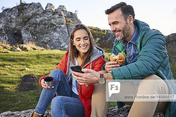 Glückliches Paar auf einer Wanderung in den Bergen macht eine Pause und schaut auf sein Handy