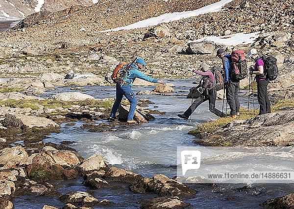 Greenland  Sermersooq  Kulusuk  Schweizerland Alps  group of people crossing brook