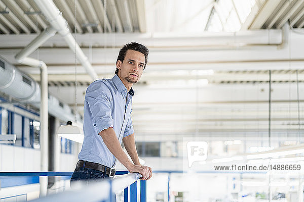 Businessman on upper floor in factory overlooking shop floor