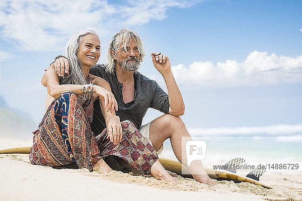 Porträt eines älteren Hippie-Paares mit Surfbrett am Strand