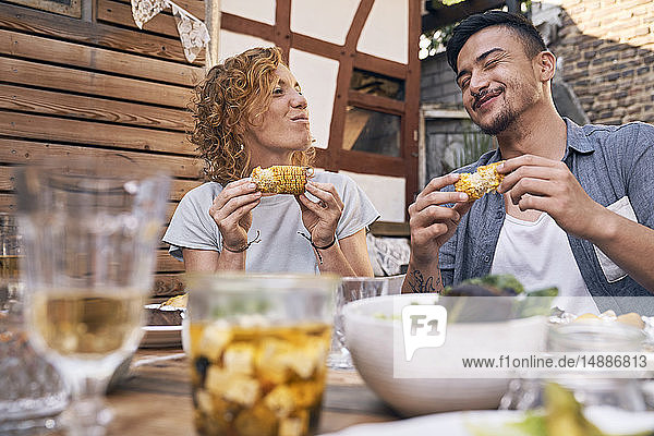 Couple eating grilled corn cobs at a backyard barbecue