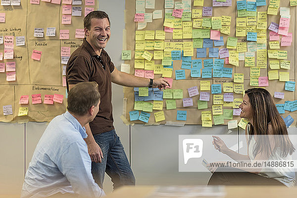 Happy colleagues discussing with sticky notes at wall in office
