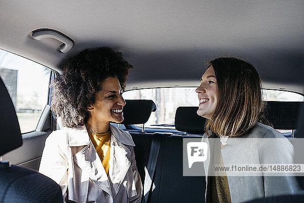 Zwei glückliche Frauen sitzen auf dem Rücksitz eines Autos