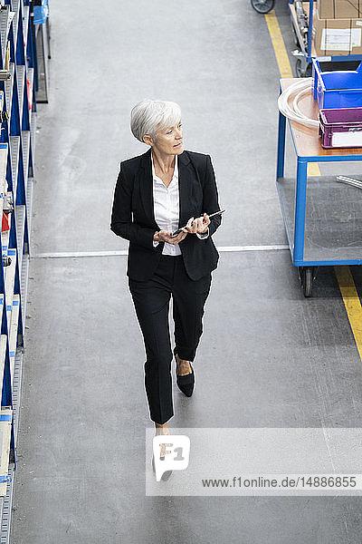 Leitende Geschäftsfrau mit Tablette in einer Fabrik