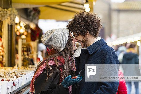 Glückliches  liebevolles junges Paar auf dem Weihnachtsmarkt