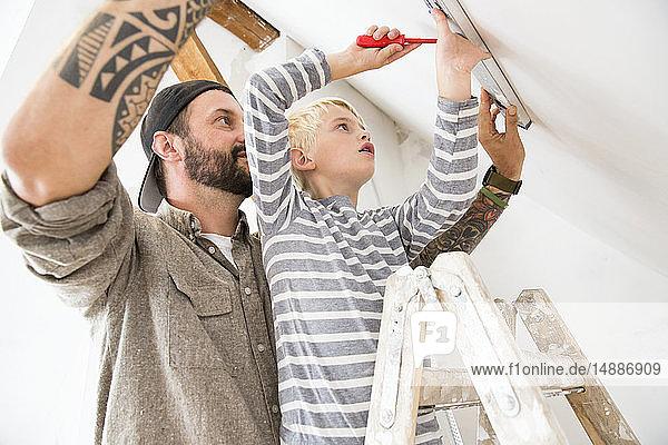 Vater und Sohn arbeiten am Dachbodenausbau unter Verwendung des Wasserstandes