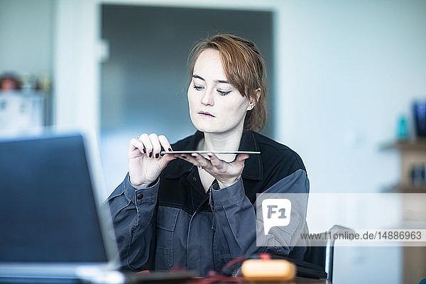 Porträt eines jungen Technikers im Rollstuhl  der Material überprüft