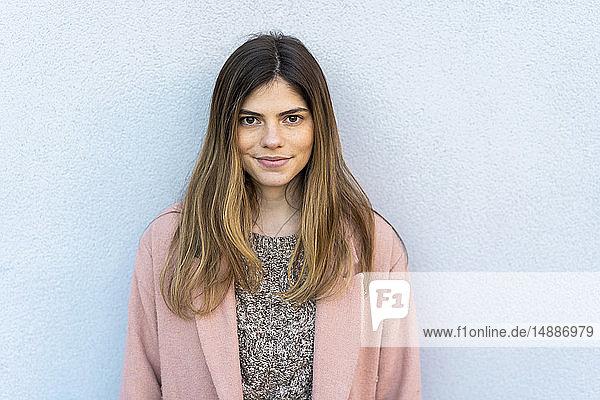 Porträt einer selbstbewussten jungen Frau an einer Wand