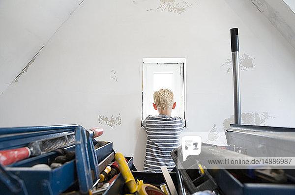 Junge schaut aus dem Fenster auf den zu renovierenden Dachboden mit Werkzeugkasten im Vordergrund