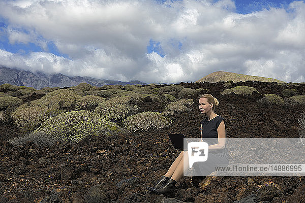 Spain  Tenerife  Malpais de Guimar  woman sitting in volcanic landscape with cacti using laptop