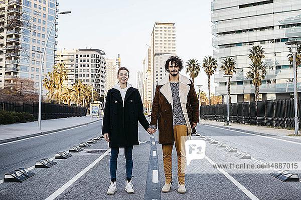 Porträt eines Paares  das sich mitten auf der Strasse an den Händen hält