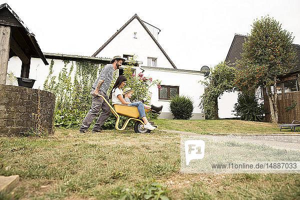Verspielter Mann schiebt Frau und Sohn in Schubkarre sitzend im Garten