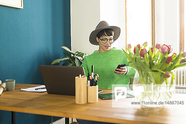 Businesswoman in home office working at her laptop and looking on her phone