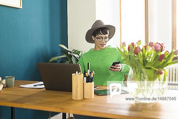 Geschäftsfrau im Home Office  die an ihrem Laptop arbeitet und auf ihr Telefon schaut