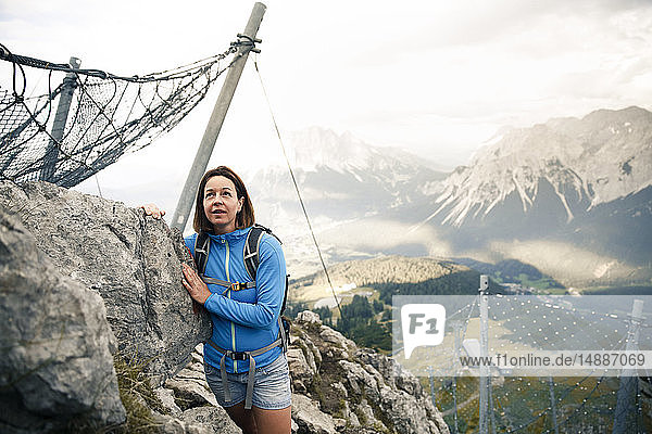 Austria  Tyrol  woman on a hiking trip in the mountains standing at rock