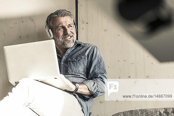 Lässiger reifer Geschäftsmann im Sitzen mit Laptop und Kopfhörern