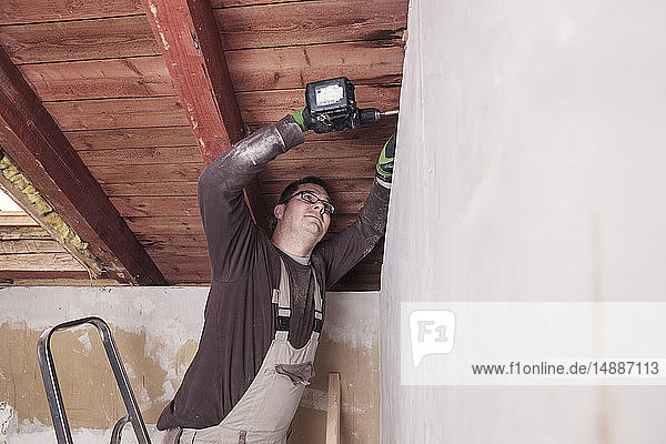 Roof insulation  worker drilling wooden board with a cordless drill
