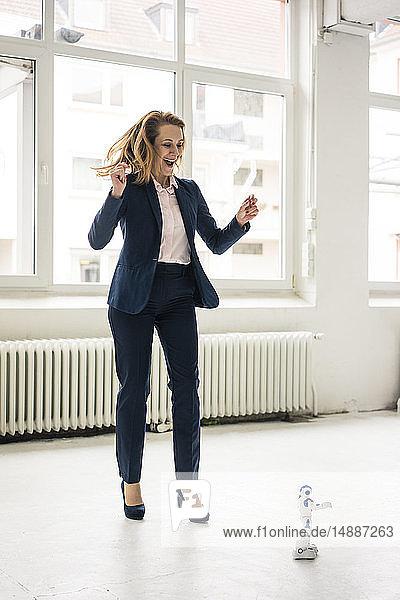 Reife Geschäftsfrau tanzt mit Spielzeugroboter