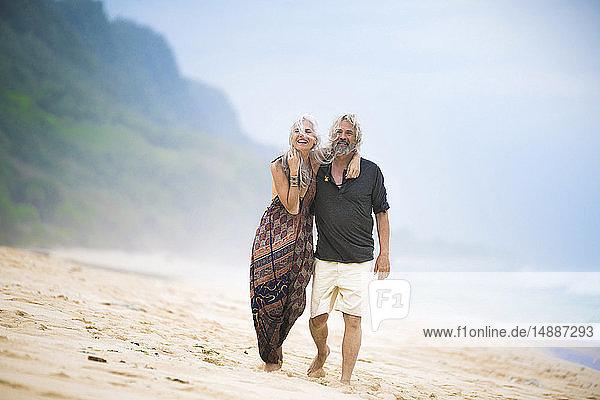 Glückliches älteres Hippie-Paar schlendert Seite an Seite am Strand
