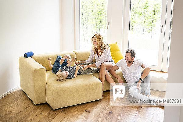 Glückliche Familie  die in ihr neues Zuhause einzieht  Eltern  die mit ihren Kindern spielen