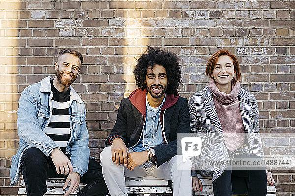 Porträt von drei glücklichen Freunden  die auf einer Bank vor einer Ziegelmauer sitzen