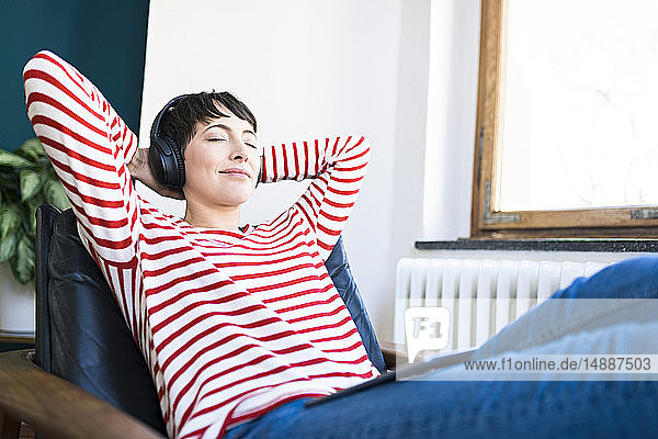 Short-haired woman with headphones relaxing in lounge chair