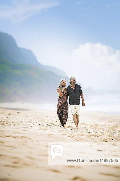 Älteres Hippie-Paar beim gemeinsamen Strandspaziergang