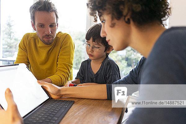 Familie am Tisch sitzend  mit digitalem Tablett