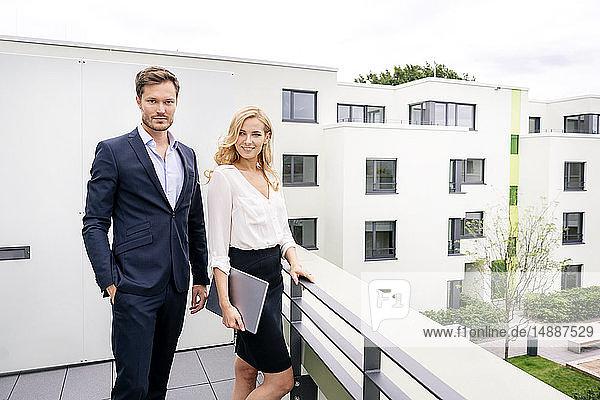Immobilienmakler steht mit Kunde auf einem Balkon und hält am digitalen Tablett