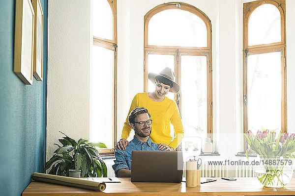 Gelegenheitsunternehmerpaar im Heimbüro  das am Laptop arbeitet und lächelt