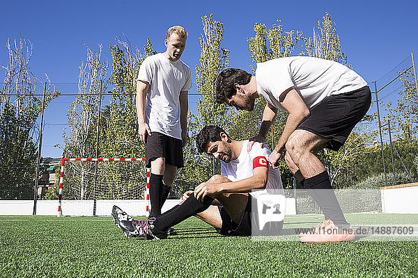 Football players helping an injured player during a match