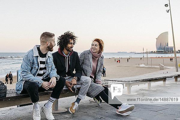 Drei glückliche Freunde sitzen auf einer Bank am Meer