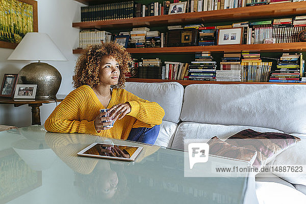 Thoughtful young woman with curly hair holding mug at home