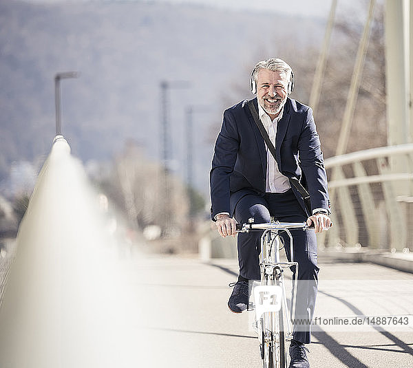 Smiling mature businessman with headphones riding bicycle on a bridge in the city