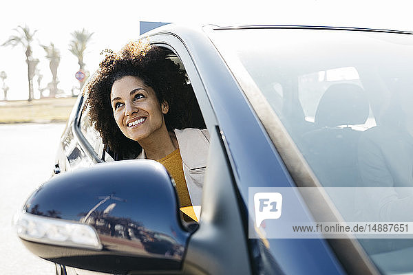 Happy woman looking out of car window