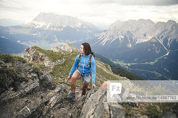 Österreich  Tirol  Frau auf einer Wanderung in den Bergen  die sich umsieht