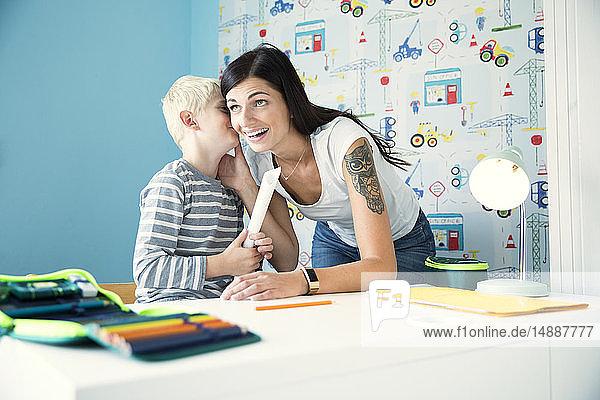 Mutter hilft Sohn bei den Hausaufgaben am Schreibtisch