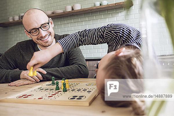 Vater und Tochter beim Brettspiel in der Küche